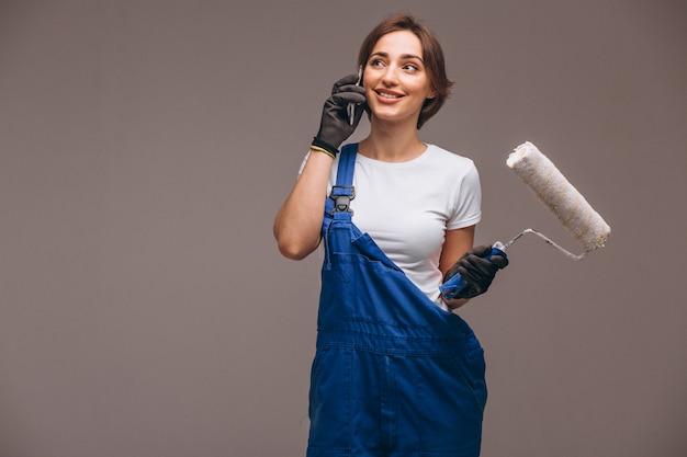 Vrouwenreparateur met het schilderen van rol geïsoleerd het spreken op de telefoon