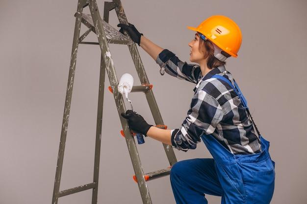 Vrouwenreparateur met ladder in een geïsoleerd uniform