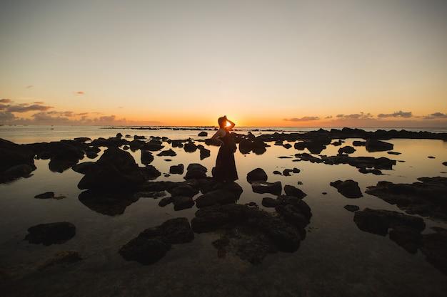 Vrouwensilhouet op de achtergrond van de indische oceaan en zwarte rotsen bij zonsondergang
