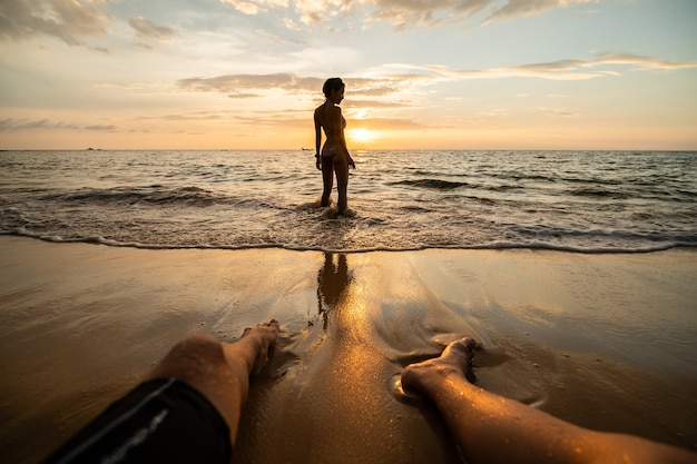 Vrouwensilhouet op het strand bij zonsondergang met mensenbenen.