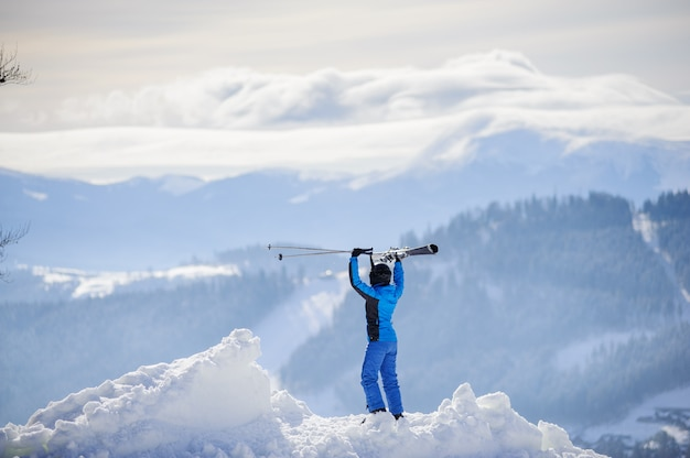 Vrouwenskiër bovenop de berg. wintersport concept