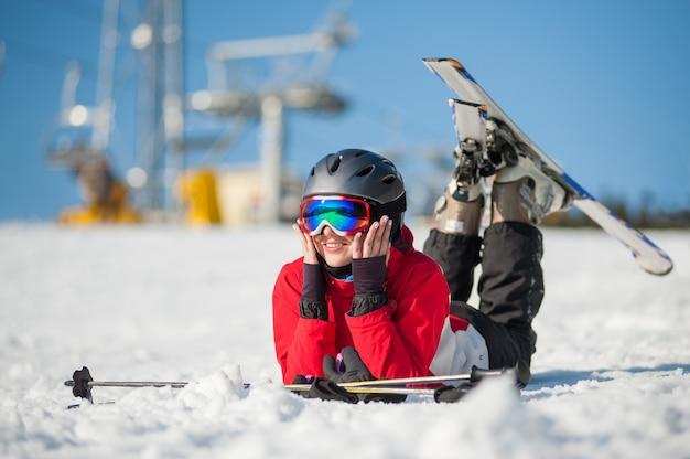 Vrouwenskiër die met skis op sneeuw bij bergbovenkant liggen