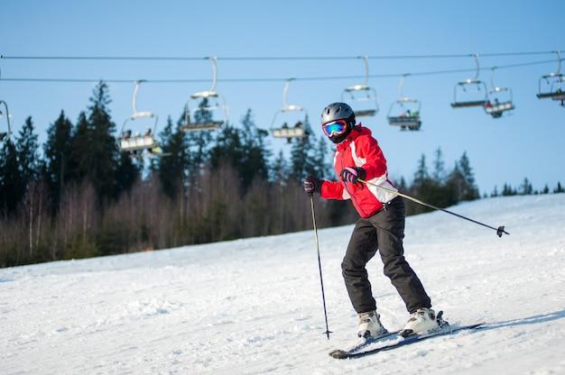 Vrouwenskiër met ski bij wijnmakerentoevlucht in zonnige dag
