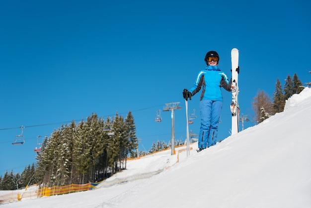 Vrouwenskiër op helling bij skiresort in de winter