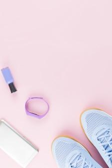 Vrouwensneakers, fitnesstracker en smartphone op pastelroze