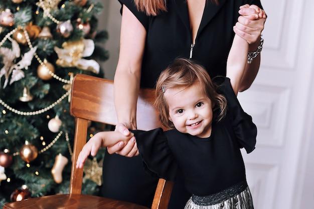 Vrouwenspelen met haar grappige lachende baby dichtbij kerstboom thuis