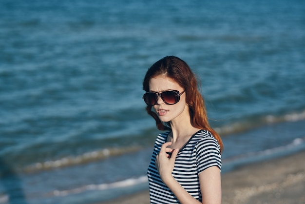 Vrouwent-shirt op het strand in de bergen dichtbij de aard van het overzeese reislandschap