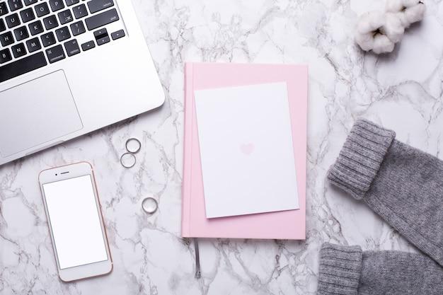 Vrouwentag met mobiele telefoon, toetsenbord en roze notitieboekje op marmeren lijst