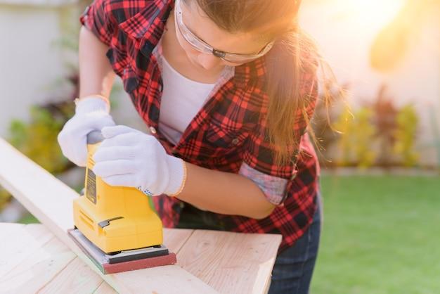 Vrouwentimmerman die met houten elektro schurende machine werken.
