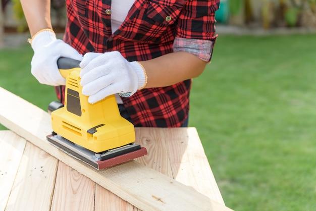 Vrouwentimmerman die met houten elektro schurende machine werken