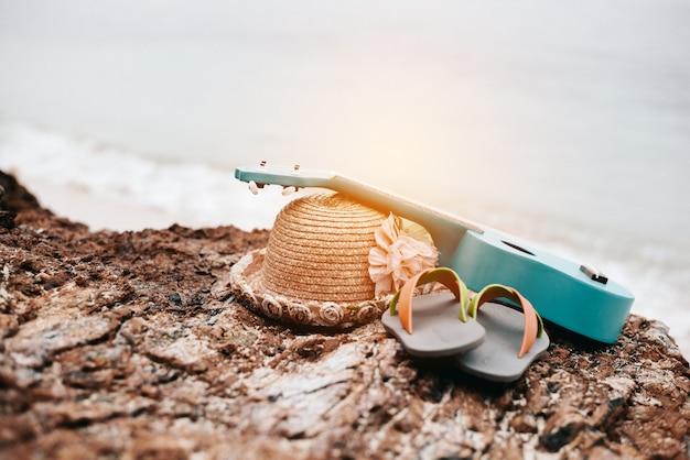 Vrouwentoebehoren in vakantie bij strand. ukelele en sandalen en hoed op rots naast zee