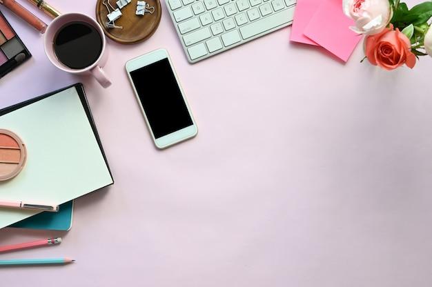 Vrouwentoebehoren op het roze bureau, inclusief toetsenbord, koffiekopje, boeket, notitieboekje, pen, mobiel, cosmetica en paperclip.