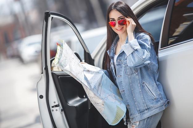 Vrouwentoerist die een kaart van de stad houden. autoreiziger navigeren in het onbekende land. meisje besturen van een auto.