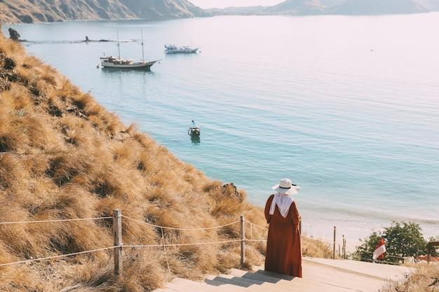 Vrouwentoerist die een zomerhoed draagt die de trap afloopt met kustachtergrond