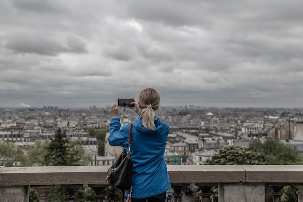 Vrouwentoerist die foto van de stad bij bewolkt weer met mobiele slimme telefooncamera neemt
