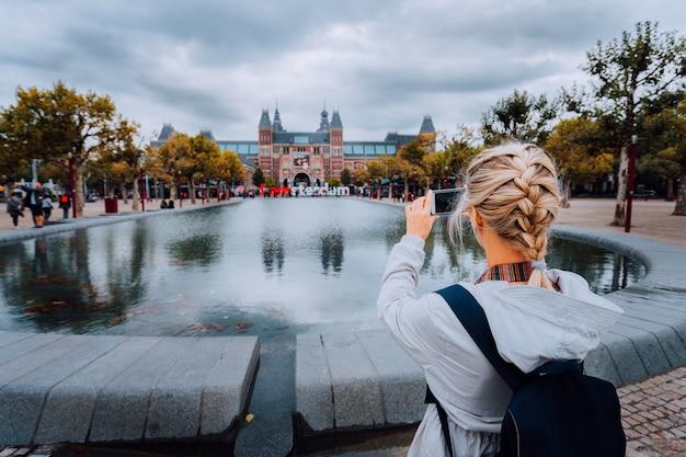 Vrouwentoerist die foto van het rijksmuseum in amsterdam op de mobiele telefoon neemt. reizen in europa citytrip concept.