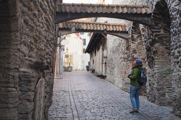 Vrouwentoerist die in de oude stad van tallinn solo reizende vakanties in de middeleeuwse straat van estland lopen