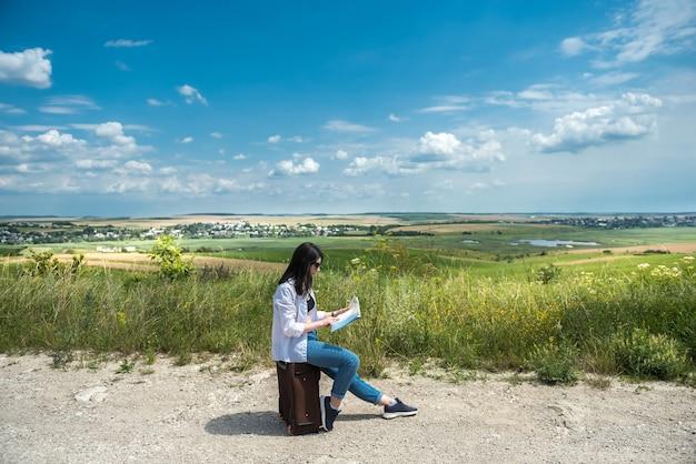Vrouwentoerist die op haar bagage zit en op de kaart kijkt om het beste weg te kiezen