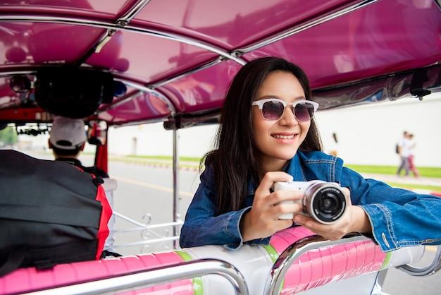 Vrouwentoerist die solo op de taxi van tuk tuk in bangkok thailand reizen