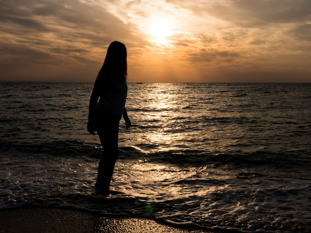 Vrouwentoerist die zonsondergang op zee bekijken. ontspanning aan zee