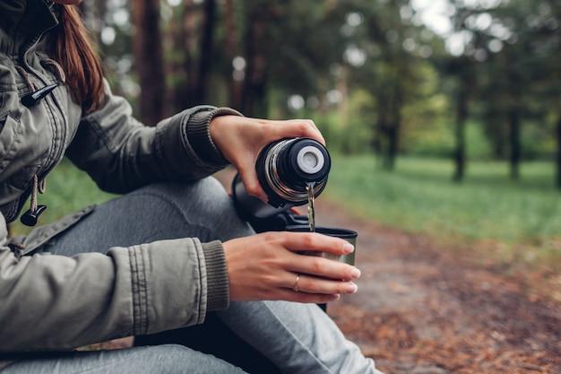 Vrouwentoerist giet hete thee uit thermos in het voorjaarsbos kamperen, reizen