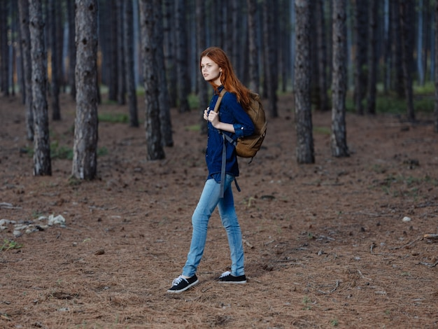 Vrouwentoerist in volle groei in een dennenbos met een rugzak op haar rug