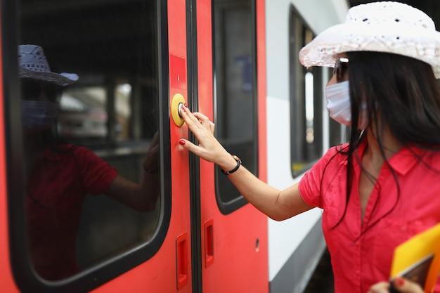 Vrouwentoerist met beschermend medisch masker die op de knop drukt om de treindeur te openen
