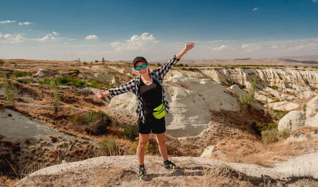 Vrouwentoerist op heuveltop met open armen tijdens bergwandeling in cappadocië, turkije