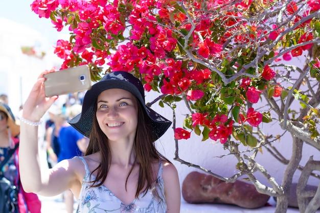 Vrouwentoerist op vakantie, die door de straten van oia in eiland santorini slenteren.