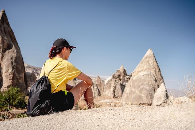 Vrouwentoerist zittend bovenop in de buurt van stenen huizen in cappadocië, turkije Premium Foto