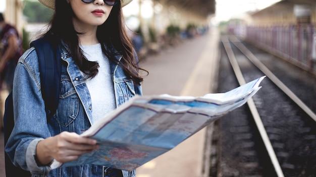Vrouwentoeristen een tas met zwarte glazen dragen, een hoed op en een kaart vasthouden bij het treinstation.