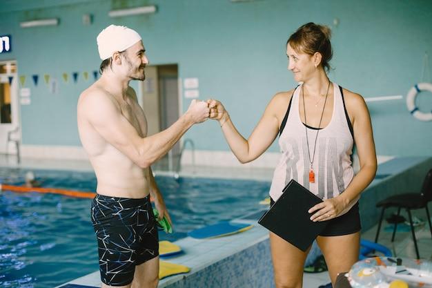 Vrouwentrainer die high five geeft aan de zwemmer. ze houdt klembord vast. succesconcept.