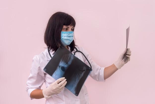 Vrouwentraumatoloog met röntgenfoto van de voet van de patiënt