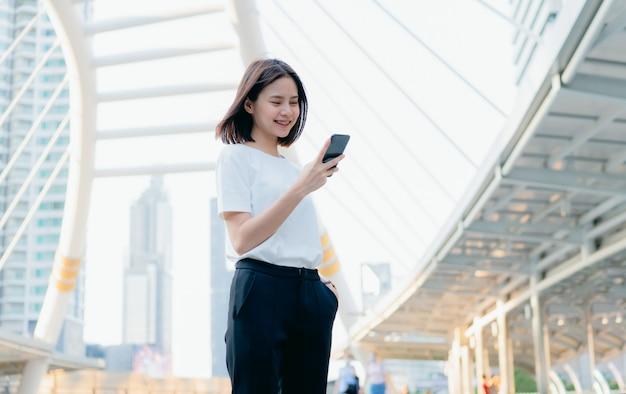 Vrouwentribune en holding een smartphone, die celtelefoon op levensstijl met behulp van.