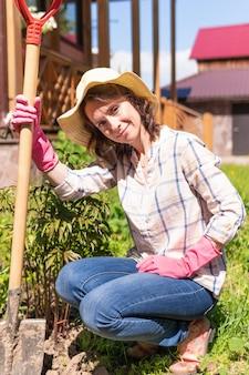Vrouwentuinman met bloemen. ze plant zaailingen in een tuin thuis. de boer houdt de spruiten vast.