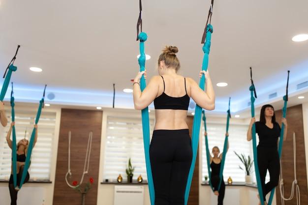 Vrouwenverblijf in hangmat die uitrekkende oefeningen van de vliegyoga in gymnastiek doen
