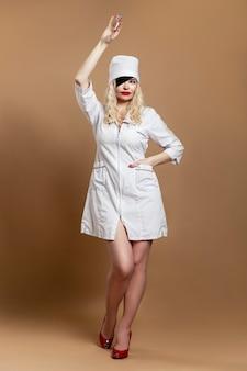 Vrouwenverpleegster met een spuit. mooie blonde met een zwart verband op haar gezicht. vaccinatie tijdens de pandemie van het coronavirus. volledige hoogte. verticaal.