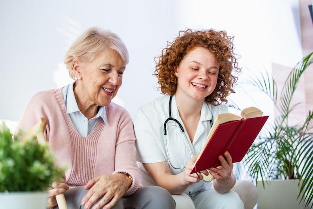 Vrouwenverzorger die een boek lezen terwijl het zitten met gelukkige hogere vrouw bij verpleeghuis.