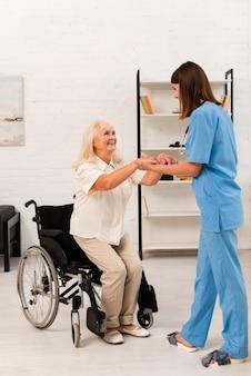 Vrouwenverzorger die oude vrouw helpen