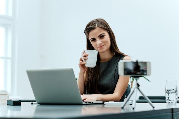 Vrouwenvlogger die registreren met telefoon.