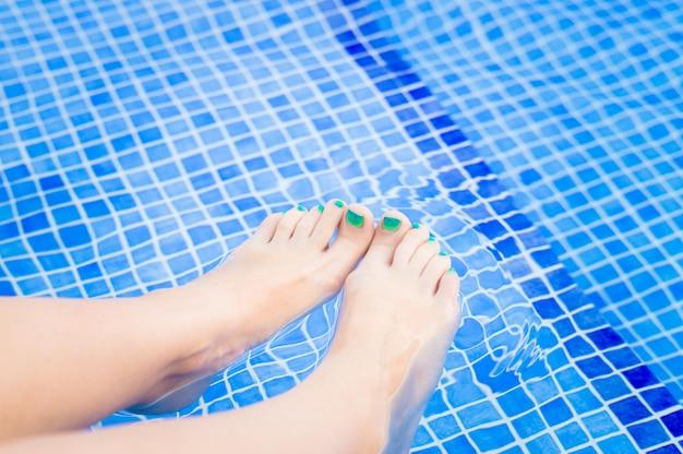 Vrouwenvoeten die in zwembad ontspannen