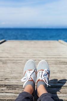 Vrouwenvoeten in vrijetijdsschoenen op de houten pier met zee- of oceaanachtergrond
