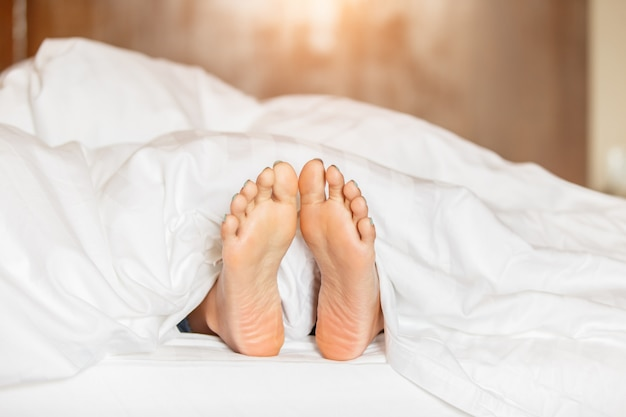 Vrouwenvoeten onder wit deken zijaanzicht