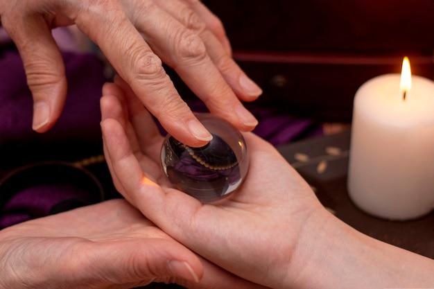Vrouwenvoorspeller legt een bal van het lot in haar hand, een magische bal van voorspellingen. het concept van het voorspellen van de toekomst, magie, occultisme. donkere achtergrond bij kaarslicht.