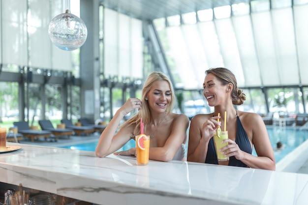 Vrouwenvrienden drinken cocktailmojito op de bar bij het zwembad, dragen een luxehotel in bikini bij het zwembad