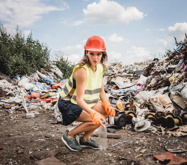 Vrouwenvrijwilliger helpt bij het schoonmaken van het veld van plastic afval. dag van de aarde en ecologie.