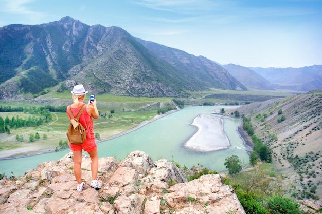 Vrouwenwandelaar die foto met slimme telefoon nemen bij bergpiek. reizen concept