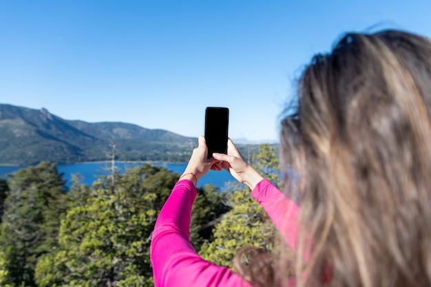 Vrouwenwandelaar die foto van een bergmeer nemen op haar smartphone