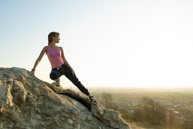 Vrouwenwandelaar die steile grote rots op een zonnige dag beklimmen. jonge vrouwelijke klimmer overwint moeilijke klimroute. actieve recreatie in de natuur concept.
