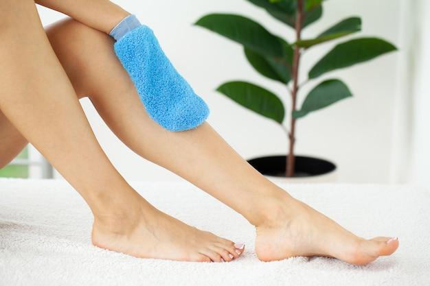 Vrouwenwapen dat blauwe droge borstel houdt om haar been te bedekken, cellulitisbehandeling en droog het borstelen.